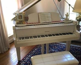 C. 1985 Howard Baby Grand Piano, larger size, excellent condition, with bench in a white case. Professionally appraised in April.