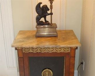 "Entry Hall: Wow!  This is a conversation piece!  This ""Russian"" chest has a faux marble top over ornate detailing and a lion head drawer pull.  The feet are hairy lion paws. The door opens to reveal  interior shelves.  The CHAPMAN mythical winged bronze lion and brass lamp is in the Hollywood Regency style and has a black paper shade."