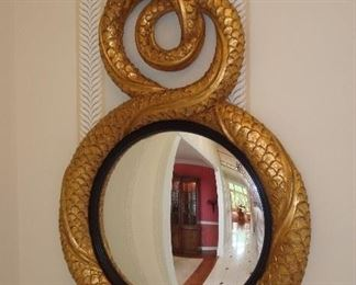 "Entry Hall:  The classic carved mirror in an antique gold frame with black trim around the mirror shows two entwined dolphins.  It measures 24"" wide x 42"" long."