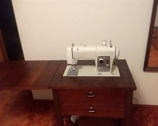 Sears sewing machine in cabinet.