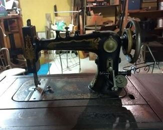 Atlantic sewing machine.  Ornate in a cabinet with foot pumping peddle.  Don't know how old it is