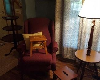 Wine colored chair with assortment of vintage tables and foot stools.