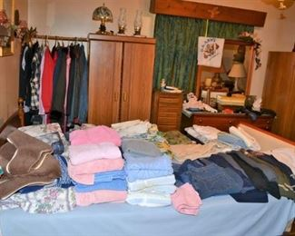 The bedroom with clothing linens, hats shoes, and tons more