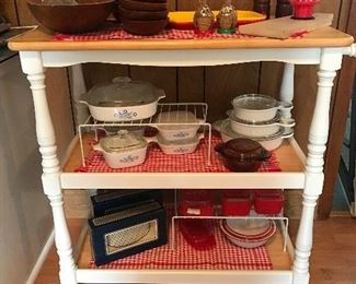 Rolling kitchen cart. Vintage Corningware - some pieces are new.  Vintage wooden wooden salad set and salt and pepper grinder. Vintage Japanese enamelware. Other new serving pieces.