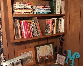 """John F. Kennedy photo and 2 brass plates featuring his profile, whimsical vintage child's desk lamp, wooden bookends with horse heads, decorative wall anchor, """"M"""" wall decor, embroidered pieces, an assortment of books on Bonsai, Italian and German recipes and  LIFE books."""