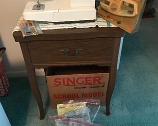 Singer sewing machine and unbranded sewing machine in cabinet. Vintage sewing notions.
