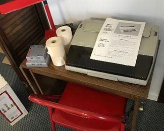 Sears & Roebuck electric typewriter and desk. Metal folding chair. Desk lamp.