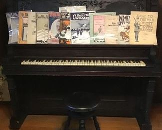 Upright piano and stool from about 1914 with some sheet music from the same era.