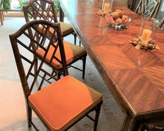 """AVAILABLE FOR PRESALE: An Asian motif extension dining table and six chairs from the Chinese Chippendale series made by Century Furniture. The set features a faux bamboo motif. There are two dining arm chairs and six side chairs, all with a Chinese Chippendale-style fretwork. The table's top surface has a patterned veneer, and two additional 18"""" leaves. The chair seats are upholstered in a burnt orange velvet fabric. on one leaf is lighter than other table surfaces. Optional china cabinet, sideboard, and mirror also available.   Dimensions 43.0"""" W x 29.5"""" H x 83.0"""" D - table dimensions noted with one leaf inserted; each leaf adds 18"""" to table size; chairs are 19″ × 39″; seat height 17""""."""