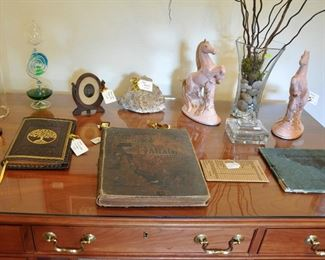 Desktop hold a copy of Dante's Paradise and Purgatory from the late 1800s and a pair of mid century pink horses.