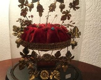 Victorian cushion with pins and more under a dome.