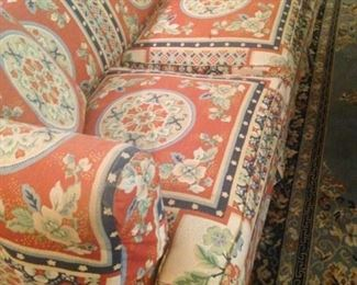 One of two matching sofa with Asian style upholstery