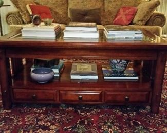 Cherry coffee table with glass top and three drawers that open from either side