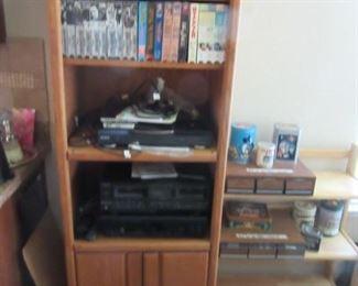 Solid oak bookcase plus VHS cassettes and electronics.