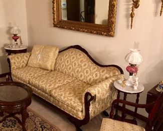 Duncan Phyfe style sofa with swan neck motif on arms & swan feet; at  far end of sofa is a matching mahogany marble top lamp table, matching cranberry lamps above sofa is a large elaborate antique frame with plate glass mirror