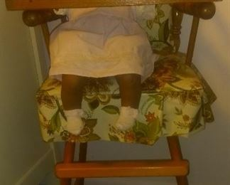 Hand crafted porcelain black baby doll.  Vintage highchair