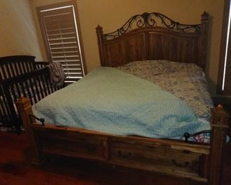 king size bed and baby crib in corner