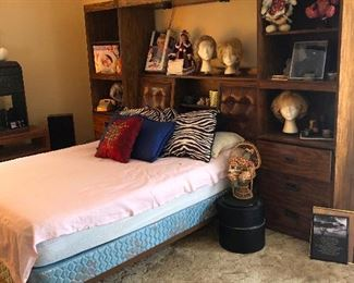 double bed with super 70s headboard that is also a console/wall unit