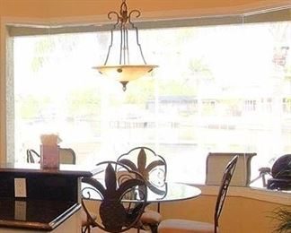 4 seat dinette with Pineapple back metal chairs and glass top round table.