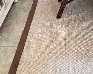 Close up of dining area woven sisal area rug with brown border
