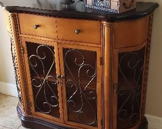 Dark wood top entry table/cabinet with one drawer and 4 metal scroll front doors. One shelf.