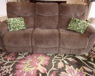 """Swivel glider chair with La-Z-Boy dual reclining sofa and Jaipur Collection by Nourison made in India 8'3"""" x 11' 6"""" thick plush area rug."""