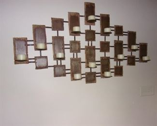 Large, cut metal wall art with candle holders.