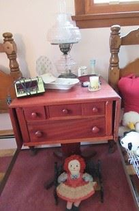 The table has drop leaves, 3 over 1 drawer. Doll is sitiing on iron bench.