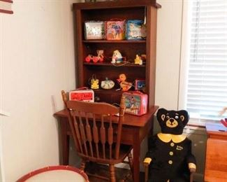 Wooden desk/cupboard with shelves holding collectible lunchboxes from the '60's-70's, and vintage pull toys