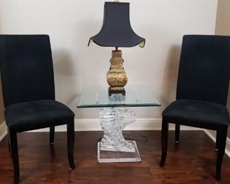 upholstered black chairs, decorative table and lamp