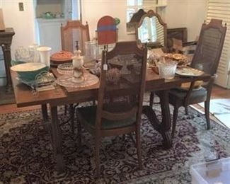 The dining room table and chairs, along with multiple kitchen serving items.