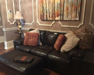 Beautiful black leather sofa and ottoman anchors an informal sitting area.