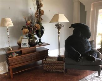 4' gorilla sits comfortably in an upholstered chair is surrounded by an art deco console table, fabulous floor lamp, end table,  and silk flower arrangements.