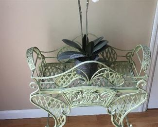 Lovely green garden table with artificial orchid flower arrangement.