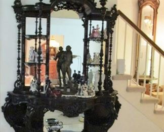 Victorian etagere on chest design with petticoat mirror , one of several bronze figures in center,  several porcelain figurines