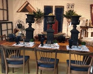 Farmhouse table and chairs with iron planters as centerpieces