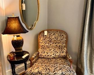 Upholstered chair with matching ottoman, round side table with inlay top and Coromandel lamp with black shade.