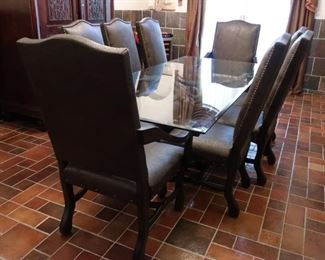 Rectangular dining table with bronze stag base and glass top with eight custom chocolate textured faux leather chairs