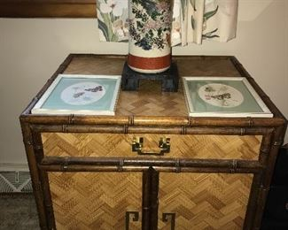 Asian-style end table with one drawer and doors below, framed butterfly prints and Asian vase.