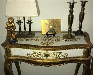 Vintage Italian gold leaf desk with one drawer, candlesticks, lamp and other decor.