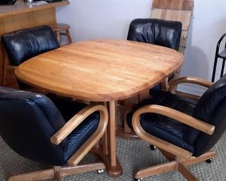 Very nice oak table with four real leather swivel chairs on casters. One leaf.