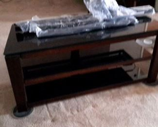 Glass top TV stand with TV brackets included.
