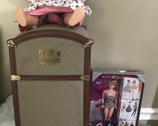 American Girl and trunk of clothes next to new Barbies