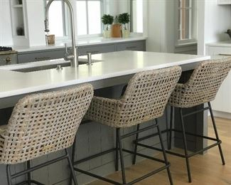 With its low contoured arms and generous seat, these Bar Stools are all about cool comfort. Hand weaved in an airy box weave of all-weather wicker with sturdy iron frame. •Washed gray resin wicker •Generously sized for comfortable lounging •Suitable for outdoor use •Micro-tufted khaki cushion •Powder-coated frame for durability •Simple assembly (top to base)