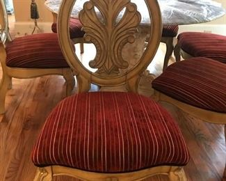6 Blonde Wood Chairs w/Carved Oval Backs. Sturdy: Carved Oval Backs in a leaf motif and upholstered fabric Cushion in red with thin black and white pinstripes Blonde Wood Carved Oval Backs in a leaf motif.