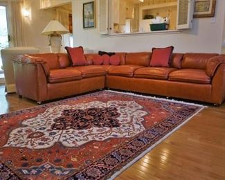 Leather sectional and one of the area rugs
