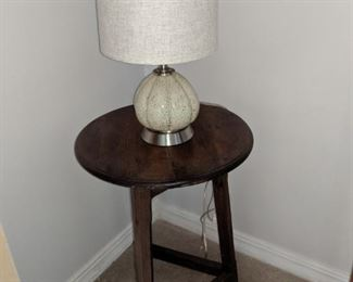Lamp. Three legged wood table.