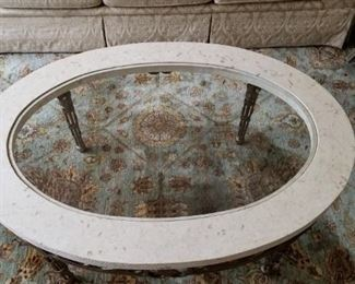 Oval coffee table with stone and glass top on iron base