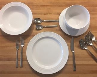 12 place settings of white stoneware;  12 place settings of 18/10 stainless flatware with serving pieces.