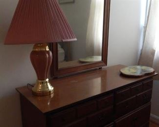 Bedroom dresser and mirror. Large pink lamp.